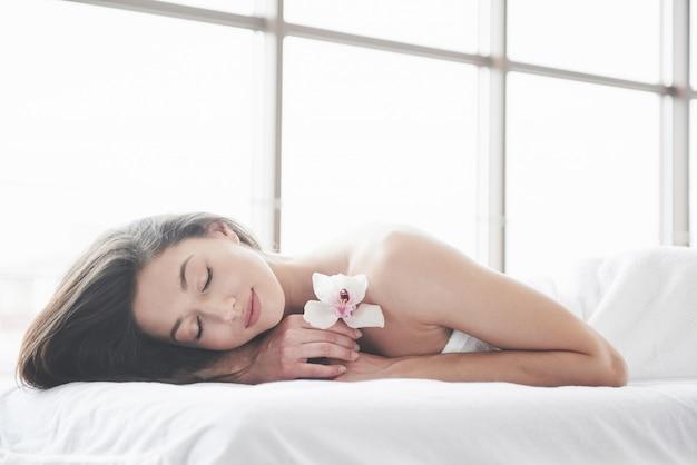 Jong mooi meisje dat op een massagelijst ligt.