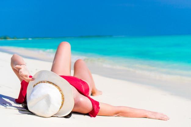 Jong mooi meisje dat op sneeuwwit tropisch strand ligt