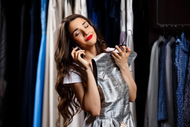 Jong mooi meisje dat op telefoon in winkelcomplex spreekt.