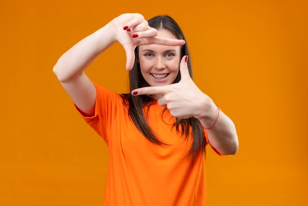 Jong mooi meisje dat oranje t-shirt draagt dat frame met handen en vingers maakt die vrolijk glimlachen die zich over geïsoleerde oranje achtergrond bevinden