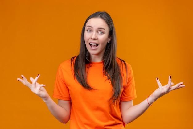 Jong mooi meisje dat oranje t-shirt draagt die wapens spreidt die verward kijken als het stellen van vraag die zich over geïsoleerde oranje achtergrond bevindt