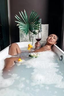 Jong mooi meisje dat terwijl het liggen in een schuimende badkuip, met een bloem en een eend stelt