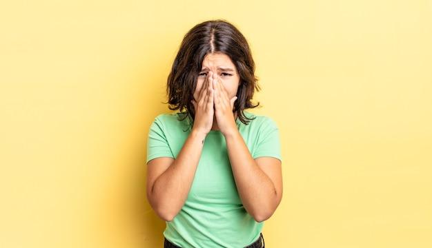 Jong mooi meisje dat zich bezorgd, hoopvol en religieus voelt, trouw bidt met ingedrukte handpalmen, smekend om vergiffenis