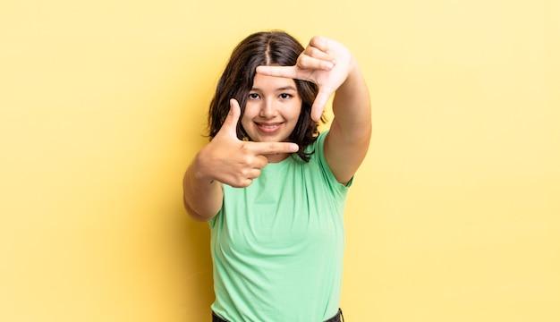 Jong mooi meisje dat zich gelukkig, vriendelijk en positief voelt, lacht en een portret of fotolijst maakt met handen