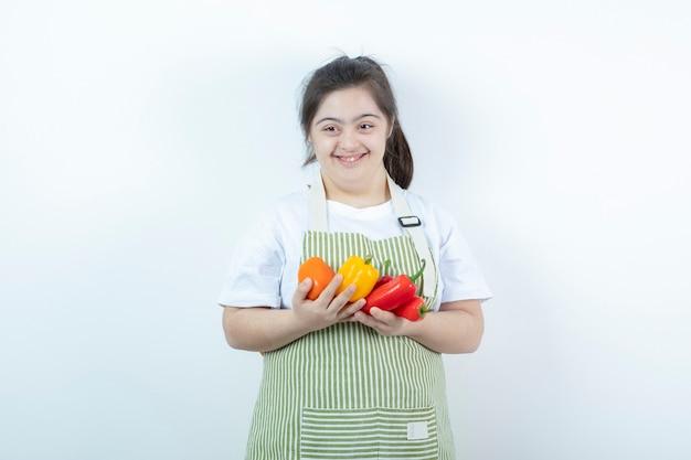 Jong mooi meisje dat zich in geruite schort bevindt en groenten houdt.