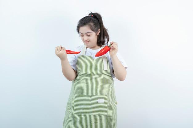 Jong mooi meisje dat zich in geruite schort bevindt en twee roodgloeiende spaanse peperpeper houdt.