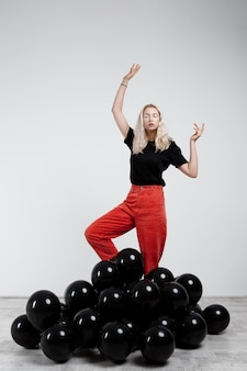 Jong mooi meisje dat zich in zwarte baloons over witte muur bevindt.
