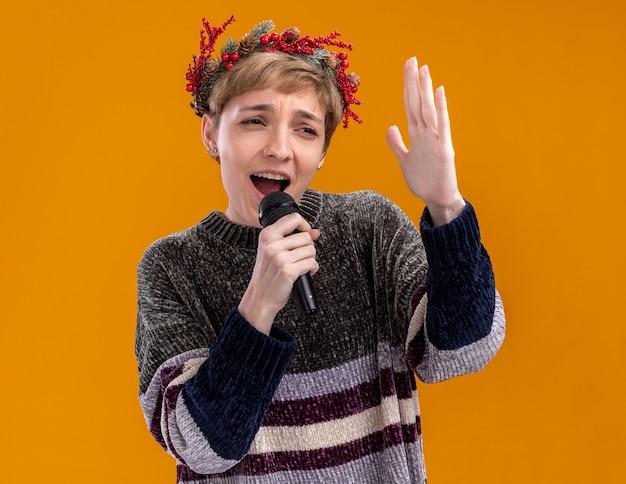 Jong mooi meisje die de microfoon van de de holdingsmicrofoon van de kerstmis hoofdkroon dichtbij mond houden die hand in lucht houden die zij zingen bekijkt dat op oranje achtergrond wordt geïsoleerd