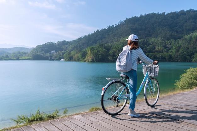 Jong mooi meisje die een fiets berijden op fietspad bij het meer in de ochtend. actieve mensen. buitenshuis