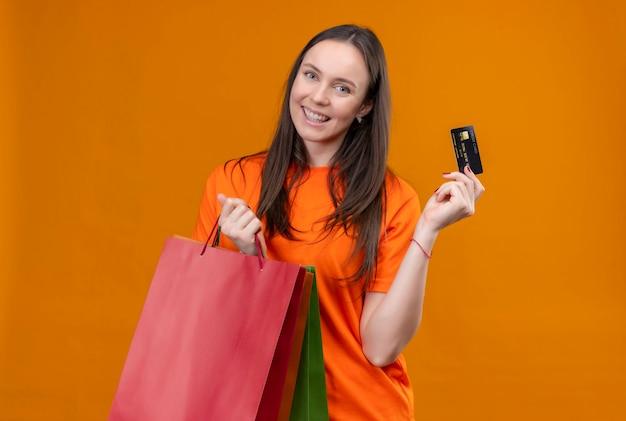 Jong mooi meisje die een oranje papieren zak van de t-shirtholding en creditcard dragen die vrolijk glimlacht status over geïsoleerde oranje achtergrond