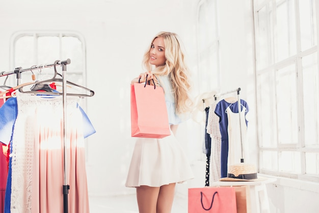 Jong mooi meisje die en op kleding bij winkel kiezen proberen
