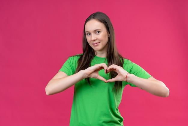 Jong mooi meisje die groene t-shirt dragen die romantisch hartgebaar over borst glimlachen maken die zich over geïsoleerde roze achtergrond bevinden