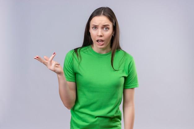 Jong mooi meisje die groene t-shirt dragen die zich met opgeheven hand bevinden zoals het stellen van vraag of het argumenteren status over geïsoleerde witte achtergrond