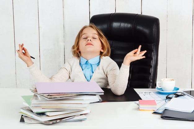 Jong mooi meisje die op werkende plaats in bureau mediteren.