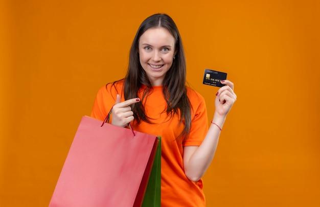 Jong mooi meisje die oranje het document pakket van de t-shirtholding en creditcard dragen die vrolijk status over geïsoleerde oranje achtergrond glimlachen