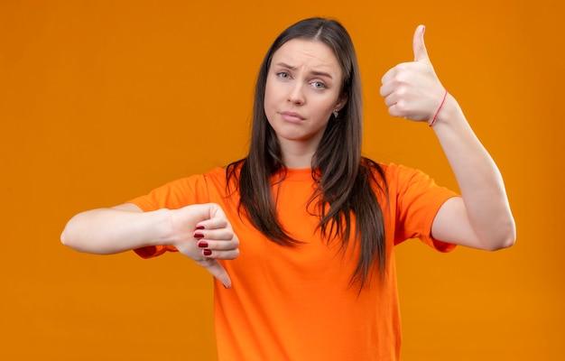 Jong mooi meisje die oranje t-shirt dragen die camera met verwarren uitdrukking bekijken die duimen op en neer tonen die zich over geïsoleerde oranje achtergrond bevinden
