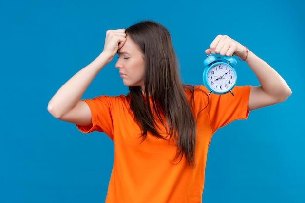 Jong mooi meisje die oranje t-shirt dragen die wekker houden die haar hoofd wegens fout slecht geheugenconcept aanraken die zich over geïsoleerde blauwe achtergrond bevinden