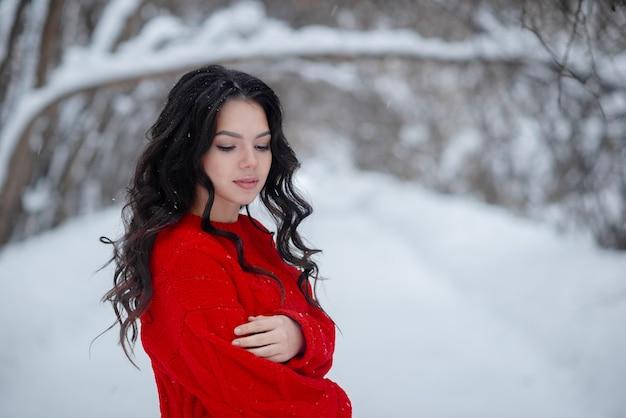 Jong mooi meisje die rode sweater in het de winterpark dragen gezond het leven en schoonheidsconcept. meisje dat pretconcept heeft. horizontale copyspace