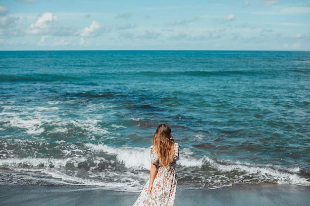 Jong mooi meisje die zich voordeed op het strand, de oceaan, golven, felle zon en gebruinde huid