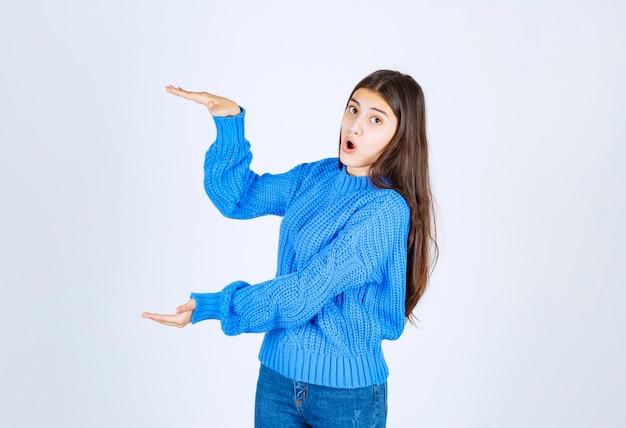 Jong mooi meisje gebaren met handen met groot en groot formaat teken.