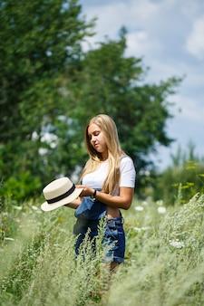 Jong mooi meisje in denim overall en een lichte hoed wandelen in het park