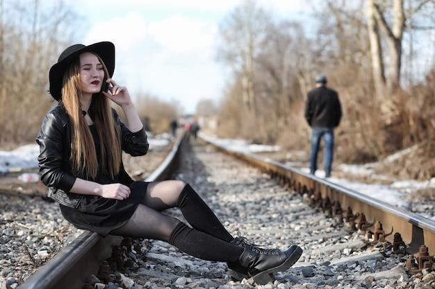 Jong mooi meisje in een hoed en met een donkere make-up buiten. meisje in de gotische stijl op straat. een meisje loopt door de stadsstraat in een leren vest met telefoon.
