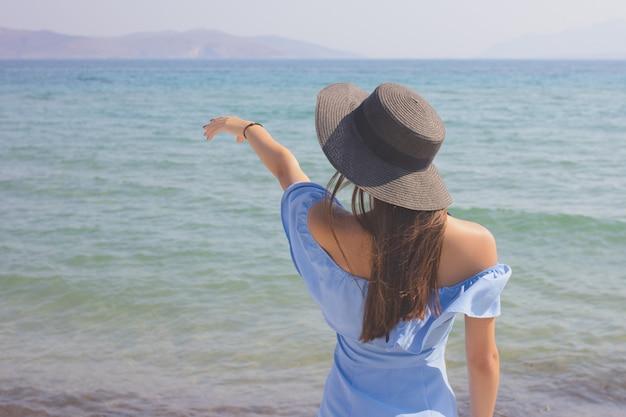 Jong mooi meisje in een hoed kijkt naar de zee, toont een hand