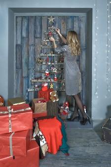 Jong mooi meisje in een schitterende jurk met kerstversiering en geschenken.