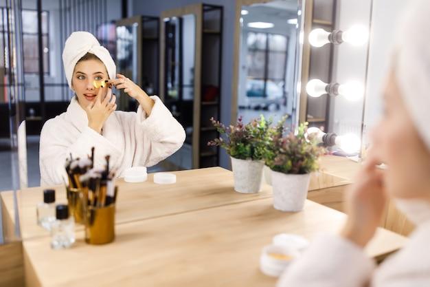 Jong mooi meisje in een wit gewaad en met een handdoek op haar hoofd legt pleisters onder haar ogen voor een spiegel