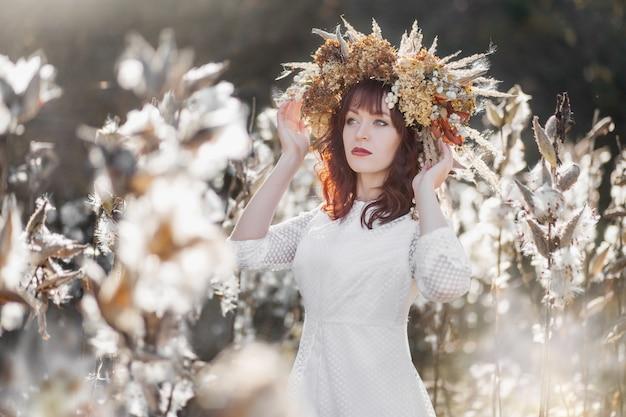 Jong mooi meisje in een witte vintage jurk en een krans van gedroogde bloemen op het hoofd in een herfst veld
