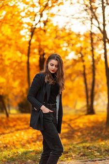Jong mooi meisje in een zwart stijlvol pak met een modieuze blazer op de natuur met heldere herfstbladeren bij zonsondergang