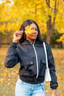 Jong mooi meisje in een zwarte casual jas en spijkerbroek met een witte handtas die haar gezicht bedekt met een geel herfstblad op gouden natuur buitenshuis