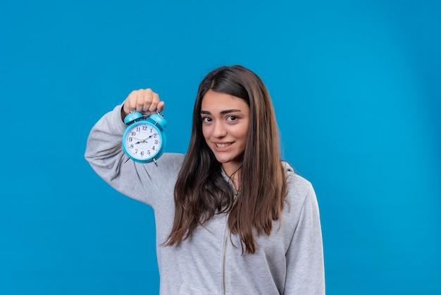 Jong mooi meisje in grijs camera kijken met glimlach op gezicht en klok staande houden over blauwe achtergrond