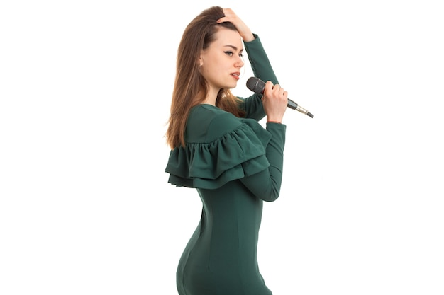 Jong mooi meisje in groene jurk zingen een karaoke met microfoon geïsoleerd op een witte achtergrond
