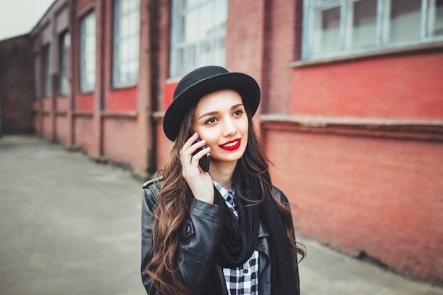 Jong mooi meisje in hoed die telefoon met behulp van vrouw die telefoon met behulp van om in de straat te telefoneren