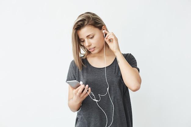 Jong mooi meisje in hoofdtelefoons glimlachen die het telefoonscherm bekijken.