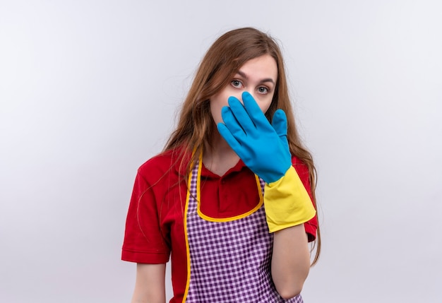 Jong mooi meisje in schort en rubberhandschoenen die mond met hand behandelen