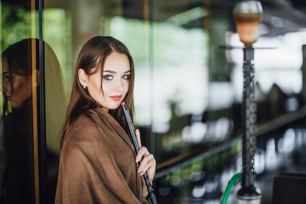 Jong mooi meisje is bedekt met een deken, staat en rookt waterpijp op het zomerterras van het moderne restaurant. gekleed in een klein zwart jurkje.