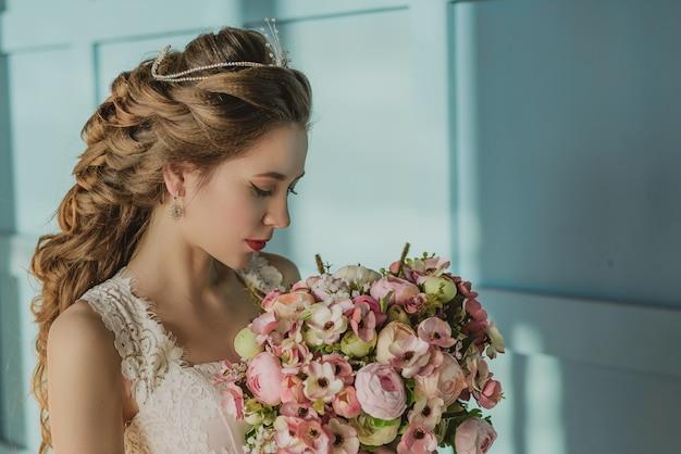 Jong mooi meisje kijkend naar een boeket bloemen, bruid