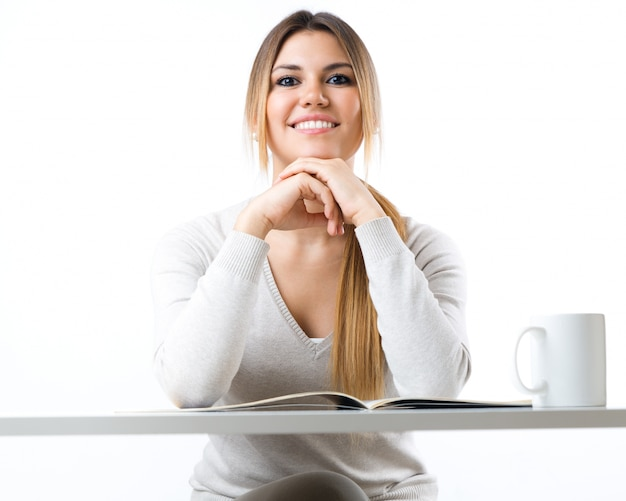 Jong mooi meisje lezen nieuws en koffie drinken. geïsoleerd