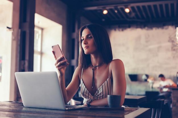Jong mooi meisje maakt gebruik van een laptop in het café, surfen op internet