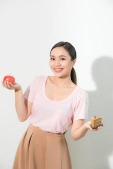Jong mooi meisje met appel en cake in haar handen