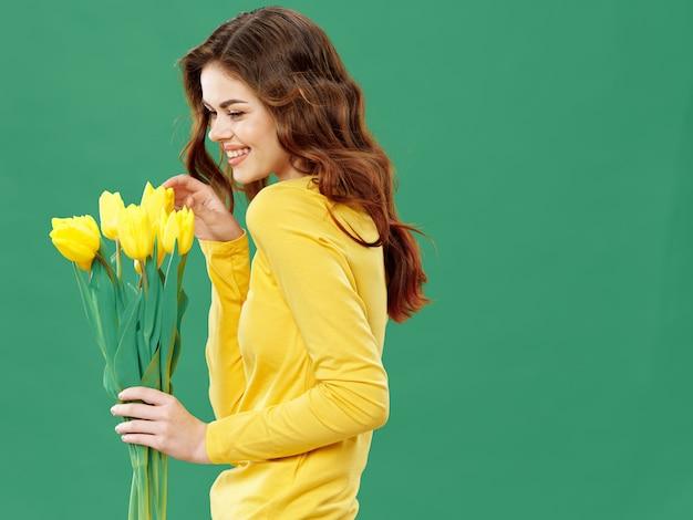 Jong mooi meisje met bloemen, vrouw het stellen met een boeket van bloemen, vrouwendag