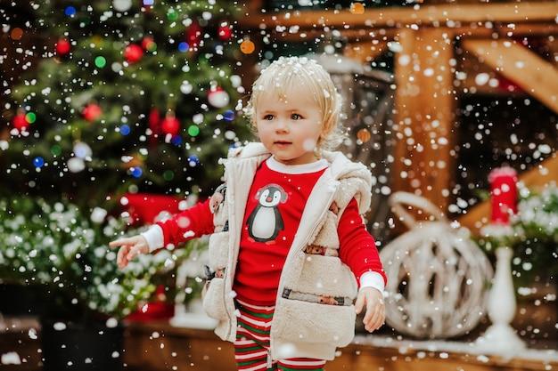 Jong mooi meisje met blond haar in winterjas vangt sneeuwvlokken tegen kerstmis achtergrond. hoge kwaliteit foto