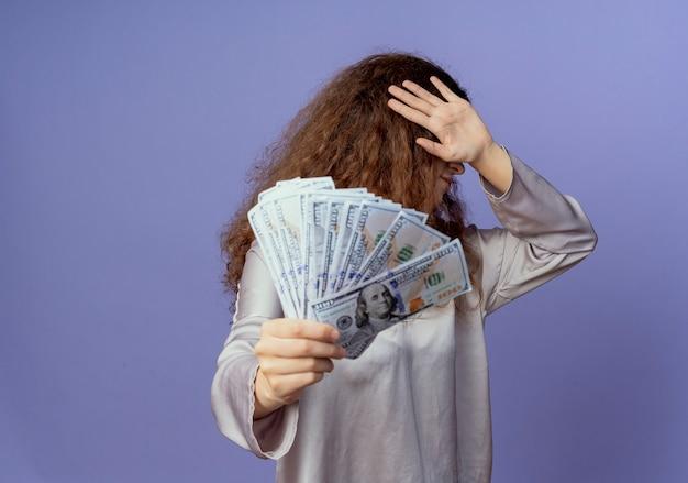 Jong mooi meisje met contant geld en bedekt gezicht met hand geïsoleerd op blauw