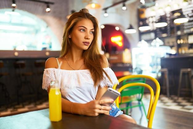 Jong, mooi meisje met een mooie glimlach zittend in een cafe limonade drinken en het gebruik van een telefoon
