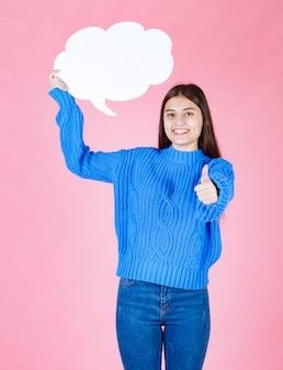 Jong mooi meisje met een witte bel voor tekst met een duim omhoog.