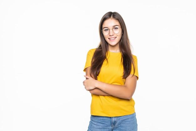 Jong mooi meisje met gekruiste handen dat op witte muur wordt geïsoleerd