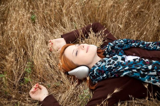 Jong mooi meisje met hoofdtelefoon die bij openlucht ligt. de tijd geel gras van de de herfstseizoen op achtergrond
