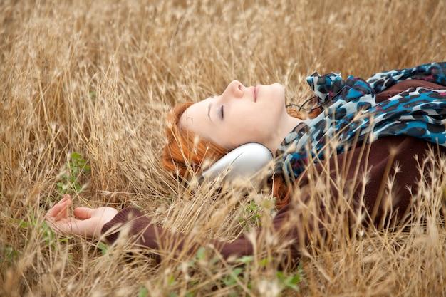 Jong mooi meisje met hoofdtelefoon die bij openlucht ligt. herfstseizoen